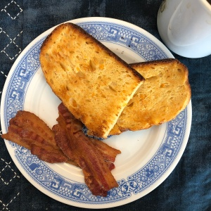 toasted apricot bread on a blue-patterned Calamityware china plate with gratuitous bacon.